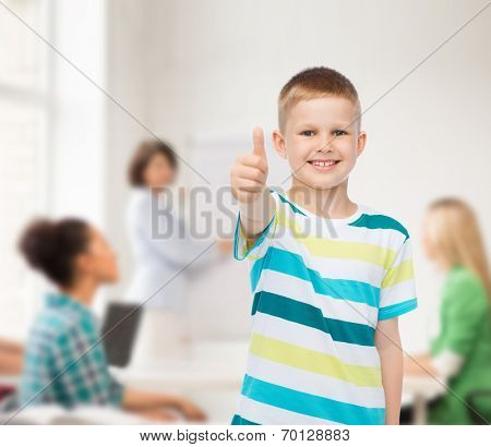 childhood, school, education and people concept - smiling little boy showing thumbs up over group of students in classroom