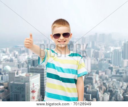 happiness, childhood, dreams and people concept - smiling little boy over green blue cloudy sky background