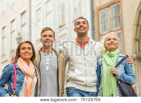 friendship, travel and vacation concept - group of smiling friends walking in the city