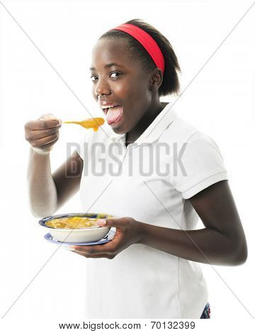 Closeup of an attractive tween enjoying pumpkin soup in celebration of Haitian Independence Day, January 1.  On a white background.