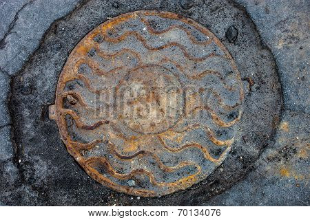 Manhole With Rusty Metal Cover In Cracked Asphalt Surface