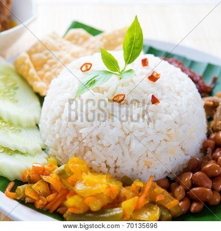 Nasi lemak kukus traditional malaysian spicy rice dish. Served with belacan, ikan bilis, acar, peanuts and cucumber.