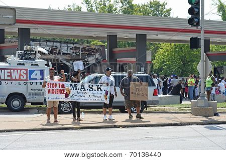 FERGUSON, MO/USA -  AUGUST 15, 2014: Group hold signs to motorists at the site of destroyed Quick Trip after Police Chief Thomas Jackson release name of officer that shot Michael Brown.