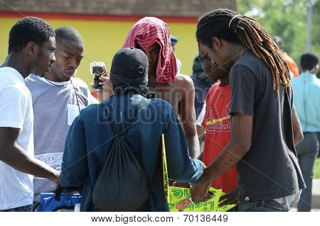 FERGUSON, MO/USA -  AUGUST 15, 2014: Men pray at the site of burnt Quick Trip after Police Chief Thomas Jackson release of the name of the officer that shot Michael Brown.