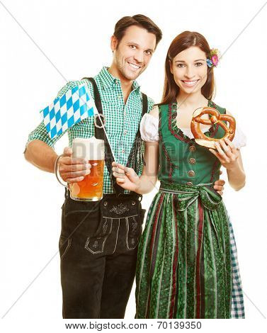 Happy couple smiling with beer and pretzel at Oktoberfest in Bavaria