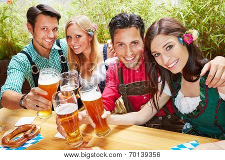 Friends in bavaria clinking beer glasses in summer in a beer garden