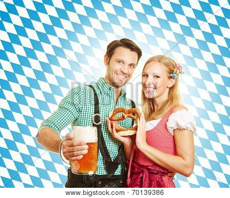 Happy couple celebrating Oktoberfest in Bavaria with beer and pretzel
