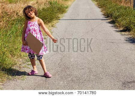 young girl, hitchhiking along a road with message board
