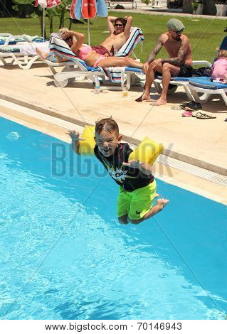 A young boy jumping into a swimming pool