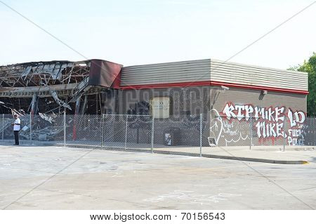 FERGUSON, MO/USA  AUGUST 15, 2014: Demonstrator stands in front of destroyed Quick Trip after Police Chief Thomas Jackson release of the name of the officer that shot Michael Brown.