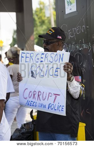 FERGUSON, MO/USA  AUGUST 15, 2014: Demonstrator holds sign at the site of destroyed Quick Trip after Police Chief Thomas Jackson release of the name of the officer that shot Michael Brown.
