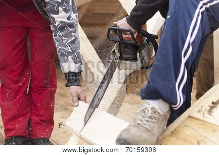Man Cutting Piece Of Wood With Chain Saw