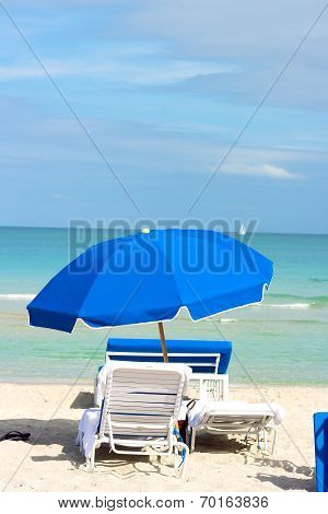 Beach chairs under blue umbrella on the ocean beach.