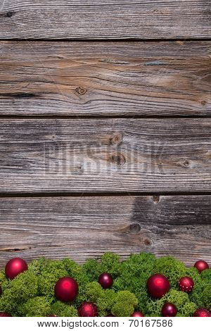 Old Background Of Wood With Red Xmas Balls And Moss.