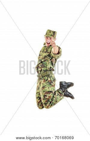Handsome Soldier In Green Camouflage Uniform And Hat Jumping Up