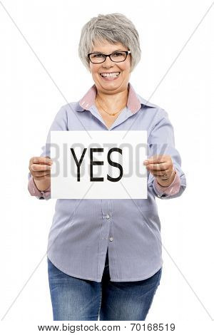 Elderly woman holding a paper card  with the word Yes
