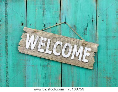 Rustic wood welcome sign hanging on weathered antique blue background