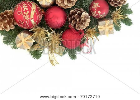 Christmas background border with bauble decorations and winter greenery over white with copy space.