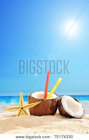 Fresh coconut cocktail on a sandy beach on a hot summer day