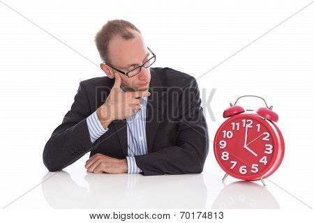 Closing Time At Four O'clock: Isolated Businessman Looking Pensive At A Red Alarm Clock.