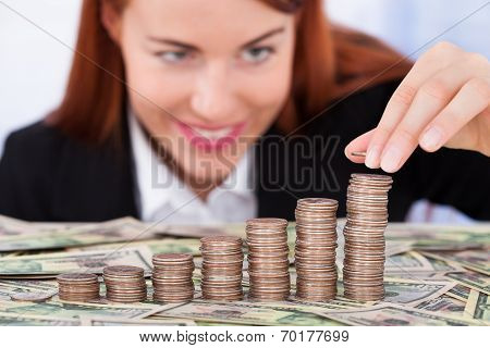 Businesswoman Stacking Coins As Bar Graph
