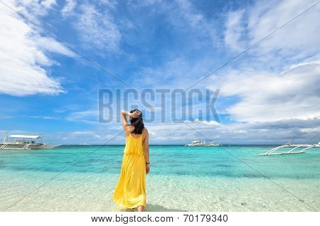 young girl walks in shallow water on tropical beach