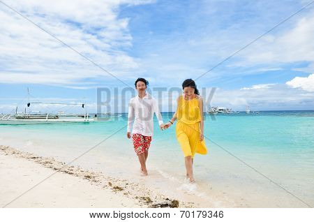 happy young couple walks in shallow water on tropical beach