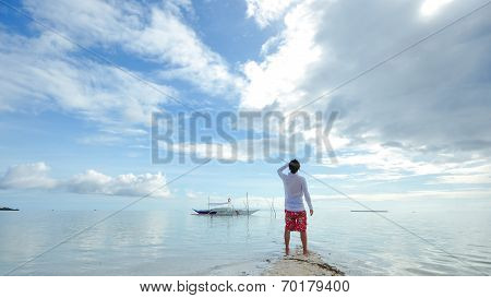 standing young man looks at horizon on beach