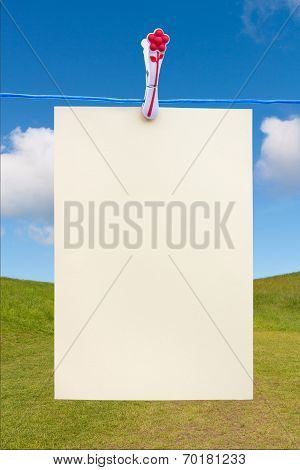 Blank Piece Of Paper On A Washing Line Against A Blue Sky And Grass Hill
