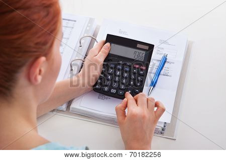 Woman Calculating Invoice At Desk