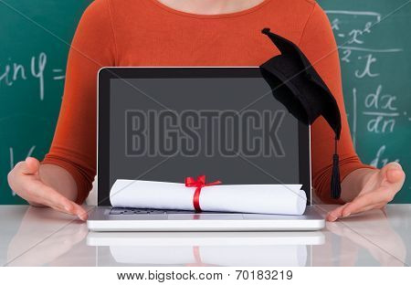 Student Showing Laptop With Mortarboard And Degree In Classroom