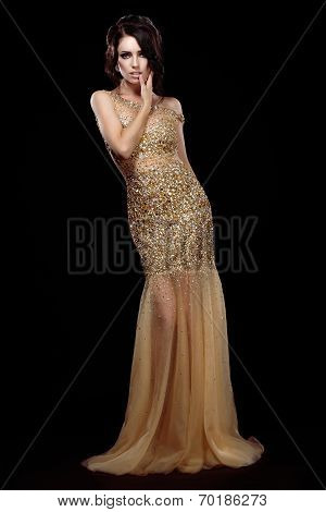 Elegance. Aristocratic Lady In Golden Long Dress Over Black Background