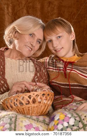 Senior woman knitting with grandson