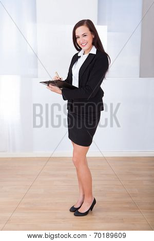 Welldressed Businesswoman Writing On Clipboard