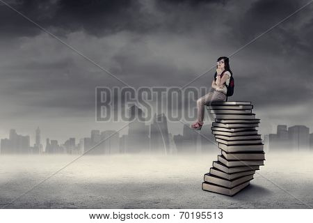 Thoughtful Student Sitting On Book