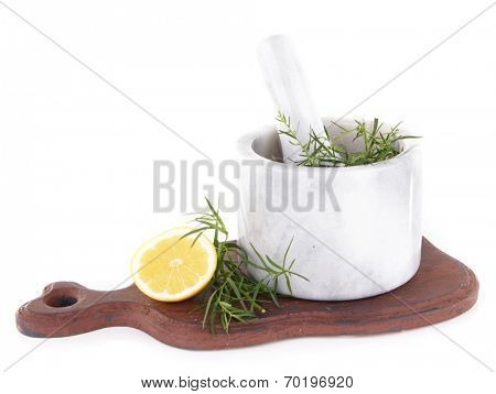 Estragon with lemon in mortar pounder on cutting board isolated on white