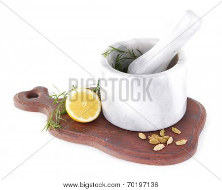 Estragon with lemon and cardamom in mortar pounder on cutting board isolated on white