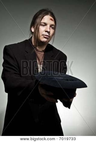 Homem com chapéu implorando por dinheiro