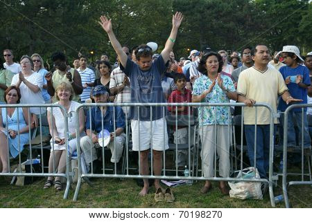 NEW YORK - JUNE 25:  A man gestures as he and others pray at the Greater New York Billy Graham Crusade in Flushing Meadow Corona Park June 25, 2005 in the Queens borough of New York City.