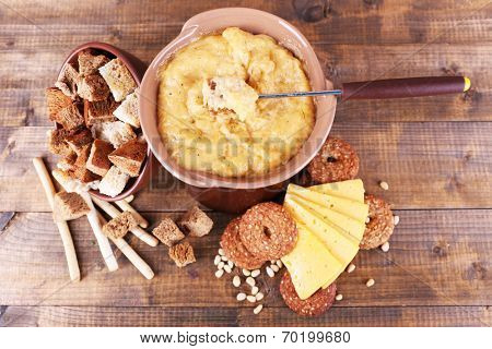 Fondue, slices of cheese and biscuits on wooden background