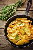pic of baked potato  - potatoes baked with rosemary on a dark wood background - JPG