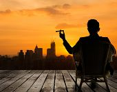 stock photo of cigar  - Silhouette of businessman sit on chair and hold a cigar and looking at the city in night - JPG