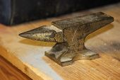picture of anvil  - A small metal anvil sitting on wooden surface - JPG