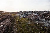 stock photo of landfill  - Piles of garbage on the city landfill near the dirt road - JPG