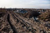 foto of landfill  - Piles of garbage on the city landfill near the dirt road - JPG