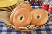 stock photo of bagel  - A basket of fresh bagels on a picnic table with fruit and plates - JPG