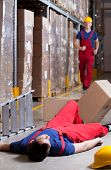image of workplace accident  - Vertical view of a warehouseman after accident at height - JPG