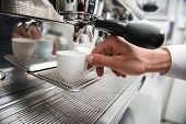 pic of metal grate  - Hands of professional barista holding two white cups on the grating of coffee machine - JPG