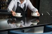picture of apron  - Barista wearing white shirt and black apron standing at the bar counter suggested us to taste his coffee