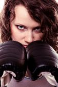 stock photo of martial arts girl  - Martial arts or emancipation idea concept. Sport boxer woman in black gloves. Fitness girl training kick boxing showing her power domination. Isolated on white background.